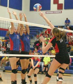 Decorah blockers Alison Stover (No. 16) and Molly Wettach (No. 8) go for the block against the New Hampton player. (Photo by Jennifer Bissell)