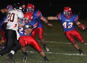 Decorah's Josey Jewell was a man possessed on the field Monday night in the Class 3A second round of the playoffs. Jewell rushed for 156 yards and led the team with 10 tackles. He is pictured gaining ground with help from blockers Drew Schwartz (No. 25) and James Ostlie. (Photo by Rick Fromm)