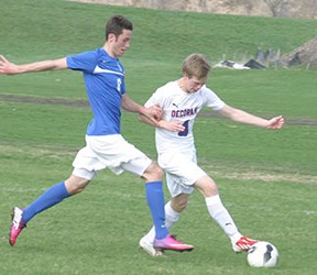 Senior Lee Rollins battles the Dubuque Wahlert player for the ball Monday. (Photo by Jennifer Bissell)