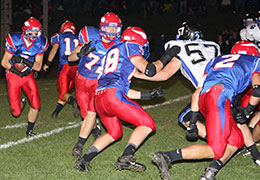 Cole Svestka (far left) takes the handoff from quarterback Bryce Pierce (No. 11) and looks to rush through a hole created by Jon Elsbernd (No. 72), Kyle Kane (No. 88) and Mikhail Suvorov (No. 2). (Photo by Rick Fromm)