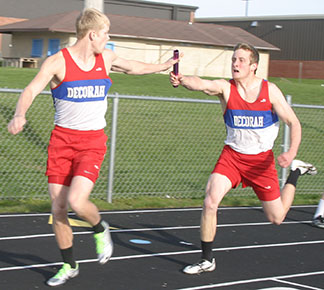 Holt Johansen (R) gets the baton to teammate Cole Svestka (L) in a recent meet.