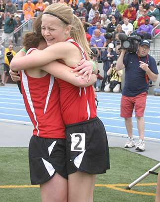 Shelby Reicks (R) gets a hug from teammate Stephanie Martin after the 4x800 set a new school record Thursday. (Photo by Jennifer Bissell)
