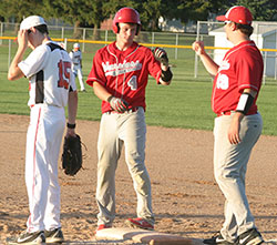 Assistant Coach Mitch Patrikus (R) congratulates Tyler Numedahl for a base hit in a recent contest. (Photo by Jennifer Bissell)