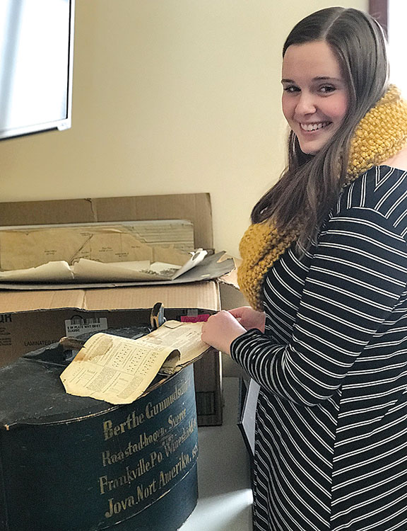 "Pictured at right with a Norwegian trunk and a music book from the late 1800s, is Luther College sophomore, Caroline Handley, who recently spent J-Term as an archivist for Aase Haugen Senior Services (AHSS). AHSS is asking the community to share information about the history of Aase Haugen and/or Aase Haugen Homes, with any artifacts that may be donated or photographed. ""Our rich history is fascinating,"" says AHSS Executive Director Jeffrey Schmidt. ""As we plan for the future and building a new facility in Decorah, we are being very thoughtful to catalog our history for posterity, and Caroline provided a great start to organizing our collection."" (Submitted photo)"
