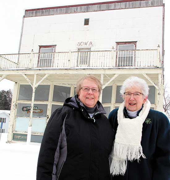 The family of the late Robert M. Brimacomb has donated the Burr Oak Mercantile building to the Laura Ingalls Wilder Park & Museum in Burr Oak. Pictured in front of the Mercantile last week are Museum Director Barb Olson, left, and Brimacomb's wife, Ferneva Brimacomb. (Decorah Newspapers photo by Sarah Strandberg)