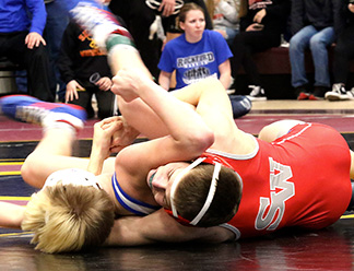 Warrior freshman Ethan Maldonado rolls Rockford's Kaden Peterson to his back for points in the first round of Saturday's district meet. (Photo courtesy of Smith Studio, Denver)