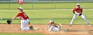 Turkey Valley's Carson Busta (2) waits for the ball with Kalvin Langreck backing up the throw as Warrior speedster Noah Tieskoetter slides safely into second base Wednesday. (Photo by Becky Walz)
