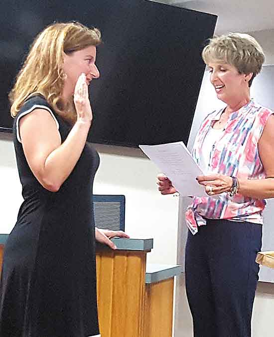 City Clerk Wanda Hemesath, right, administers the oath of office to Emily Neal after Neal was appointed to fill a vacancy on the Decorah City Council Monday night. (Photo by Sarah Strandberg)
