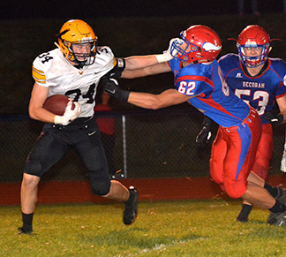 Decorah's Mason O'Hara (62) gets a hand on the Go-Hawk ball carrier in the backfield as well as a hand to his face mask. Also pictured is David Johanningmeier (53). (Photo by Becky Walz)